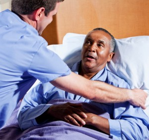 Male nurse (30s) helping African American senior man (60s) in hospital bed.