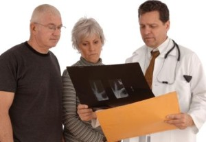 Doctor reviewing X-Ray film with senior couple on a white background